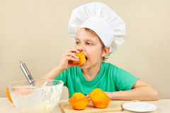Little funny chef is tasting cooked homemade cake Royalty Free Stock Image