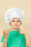 Little funny chef is tasting cooked pizza Royalty Free Stock Images