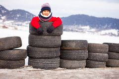 Little funny child in red jacket standing inside used tires among the road mountain view on background royalty free stock images