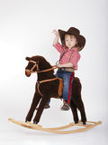 Little funny cowgirl riding horse Stock Photos