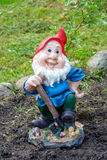 Little funny garden gnome in the garden Stock Photo