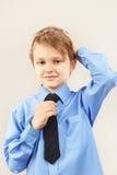 Little funny gentleman straighten tie over bright shirt Stock Photos