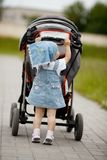 Little funny girl with baby carriage Stock Photo