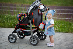 Little funny girl with baby carriage Royalty Free Stock Image
