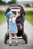 Little funny girl with baby carriage Stock Photos