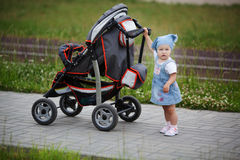 Little funny girl with baby carriage Stock Photography