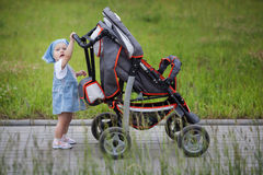 Little funny girl with baby carriage Royalty Free Stock Photo
