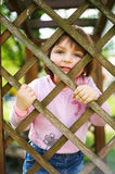 Little funny girl behind the fence Royalty Free Stock Images