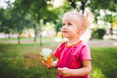 Little funny girl blonde eating sweet blue ice cream in a waffle cup on a green summer background in the park. smeared her face an. D cheeks and laughs. Dressed Royalty Free Stock Photography
