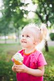 Little funny girl blonde eating sweet blue ice cream in a waffle cup on a green summer background in the park. smeared her face an Royalty Free Stock Photos