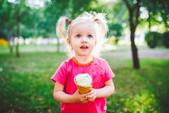 Little funny girl blonde eating sweet blue ice cream in a waffle cup on a green summer background in the park. smeared her face an. D cheeks and laughs. Dressed Stock Photos