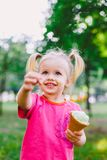 Little funny girl blonde eating sweet blue ice cream in a waffle cup on a green summer background in the park. smeared her face an. D cheeks and laughs. Dressed Stock Photo