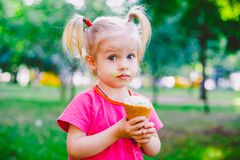 Little funny girl blonde eating sweet blue ice cream in a waffle cup on a green summer background in the park. smeared her face an. D cheeks and laughs. Dressed Stock Image