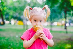 Little funny girl blonde eating sweet blue ice cream in a waffle cup on a green summer background in the park. smeared her face an. D cheeks and laughs. Dressed Royalty Free Stock Images