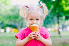 Little funny girl blonde eating sweet blue ice cream in a waffle cup on a green summer background in the park. smeared her face an. D cheeks and laughs. Dressed Stock Photography
