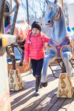 Little funny girl on carousel at an amusement park Stock Image
