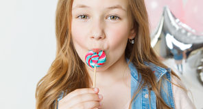 Little funny girl with colorful lollipop in her mouth. Balloons on background Royalty Free Stock Photos