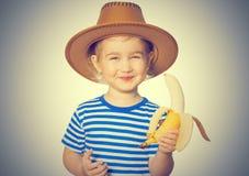 Little Funny girl eats banana. Stock Photo