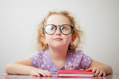A little funny girl with glasses is going to read a book.  stock photography