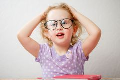 Little funny girl with glasses holding her head.  royalty free stock image