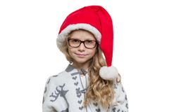 Little funny girl with glasses, Santa Claus hat, sweater with deer, isolated on white background.  royalty free stock photography