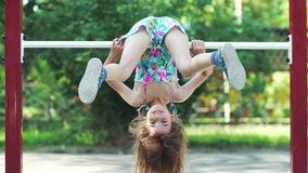 Little funny girl hanging upside down on the horizontal bar. slow motion