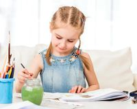 Little girl isdraws with watercolors stock photography