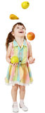 Little funny girl juggles fruit Royalty Free Stock Photo