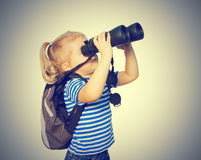 Little Funny girl looking through binoculars. Stock Image
