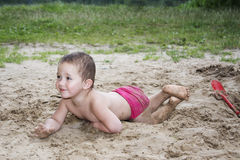 Little funny girl lying on the sand near the lake in summer and Royalty Free Stock Photos