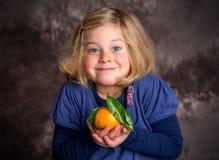 Little funny girl with mandarin orange Stock Photos