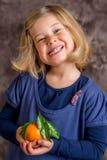 Little funny girl with mandarin orange Royalty Free Stock Image