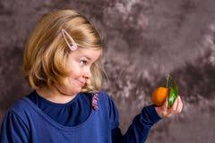Little funny girl with mandarin orange Royalty Free Stock Photo