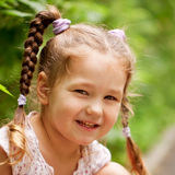 Little funny girl with pigtails outdoors Royalty Free Stock Photo