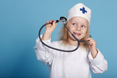 Little funny girl playing nurse. Studio photo Royalty Free Stock Images
