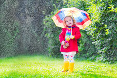 Little funny girl playing in the rain. Funny cute curly toddler girl wearing red waterproof coat and yellow rubber boots holding colorful umbrella playing in the Royalty Free Stock Photos