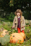 Little funny girl with pumpkins Stock Image