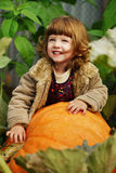 Little funny girl with pumpkins Stock Photo
