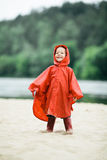 Little funny girl with raincoat Stock Photos