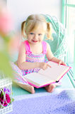 Little funny girl reading book near window Royalty Free Stock Photography