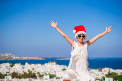 Little funny girl in red Santa hat outdoors background of Mykonos. Kid at street of typical greek traditional village Stock Image