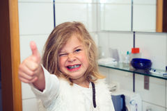 Little funny girl with retainer and thumb up. Looking in to the camera Royalty Free Stock Image