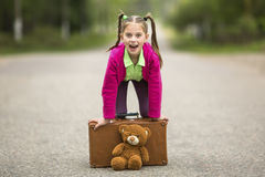 Little funny girl on the road with a suitcase and a Teddy bear. Happy. Little funny girl on the road with a suitcase and a Teddy bear Royalty Free Stock Photography