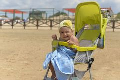 A little funny girl sitting in a wheelchair on the sandy shore royalty free stock photo