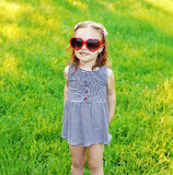 Little funny girl in sunglasses on the grass Royalty Free Stock Image