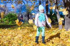 Little funny girl throws autumn leaves in park on Royalty Free Stock Photos