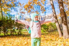 Little funny girl throws autumn leaves in park on Royalty Free Stock Image
