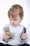 Little funny girl with two mobile phones. On white Royalty Free Stock Photos