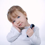 Little funny girl with two mobile phones. On white Royalty Free Stock Images