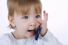 Little funny girl with two mobile phones Stock Photography
